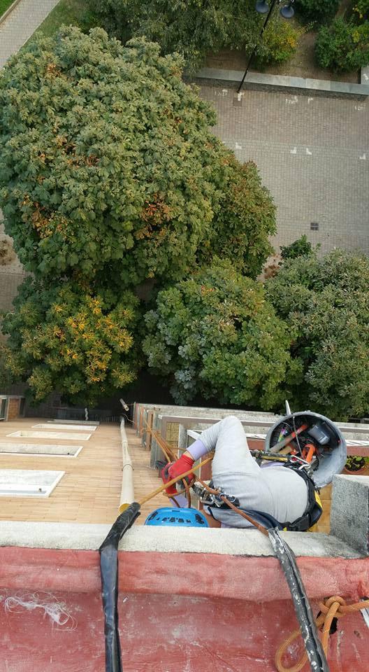 vista dall`alto di un edificio mentre un addetto lavora su una superficie tenuto da una fune protettiva