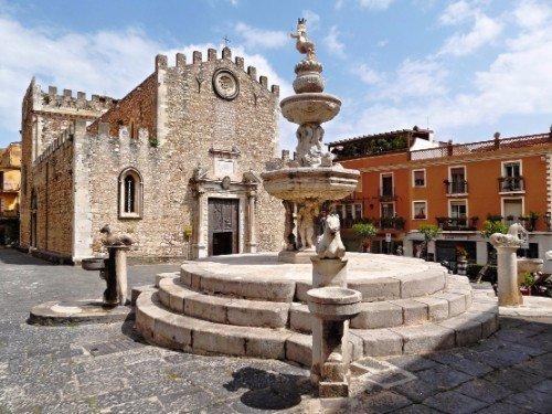 una fontana antica davanti a una cattedrale