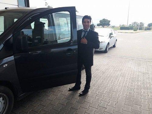 un uomo con un completo accanto a un'auto con la porta aperta