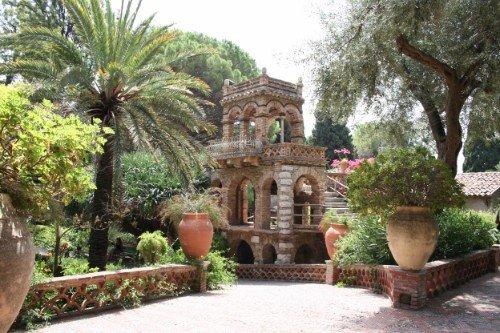 un piccolo monumento in un giardino con alberi e palme