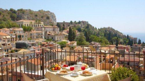 un tavolo apparecchiato in una terrazza con vista di una cittadina e delle colline
