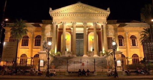un palazzo con delle colonne e delle luci durante la sera