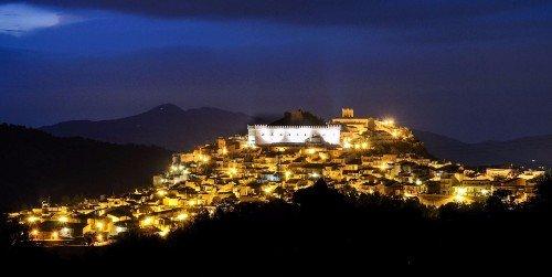 una città illuminata e vista delle montagne