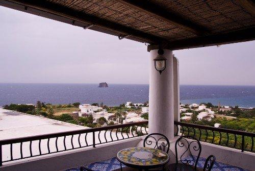 dei tavoli e delle sedie in una terrazza con vista del mare
