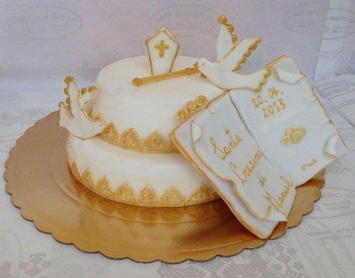 una torta a due piani con una croce e due colombe in tema Cresima