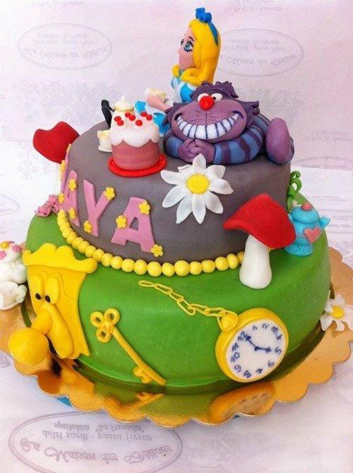 una torta a due piani ricoperta di glassa di color verde e grigia scura con i personaggi di Alice nel paese delle meraviglie