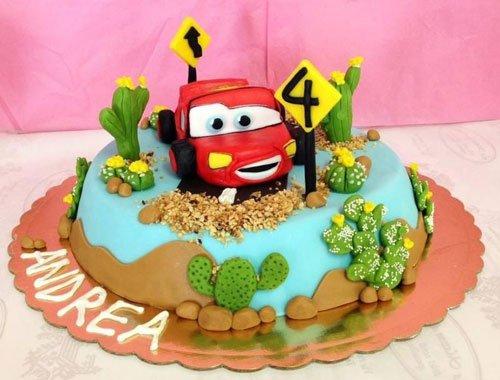 una torta ricoperta da glassa azzurra con sopra una macchinina rossa del film Disney Cars e sulla sinistra la scritta Andrea