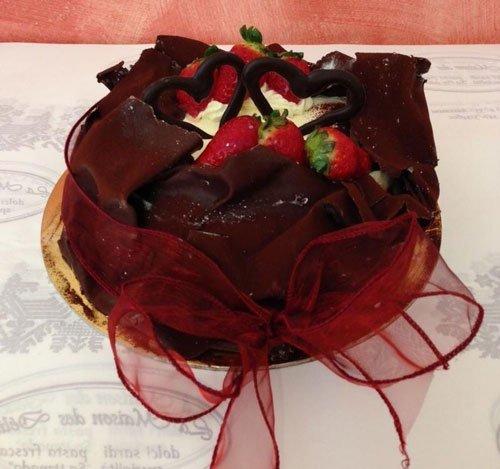 Una torta al cioccolato con delle fragole e un fiocco bordeaux
