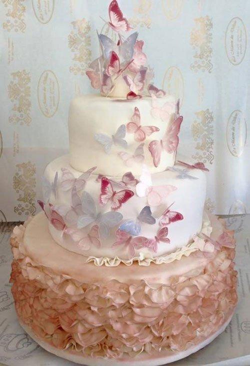 una torta a tre piani alla panna coperta di fiori e farfalle colorate di glassa