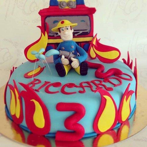 una torta ricoperta di glassa azzurra e fiamme con sopra un omino pompiere e dietro il camion