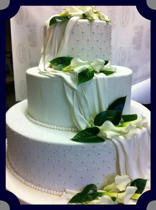 una torta a tre piani con dei tulipani bianchi