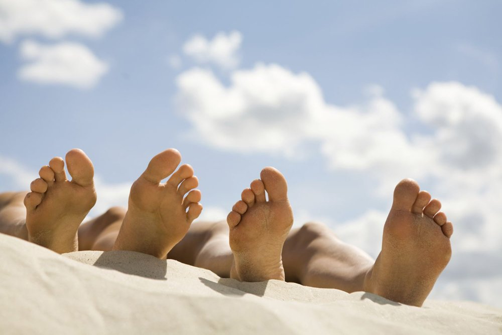 The feet of two people lying on the beach