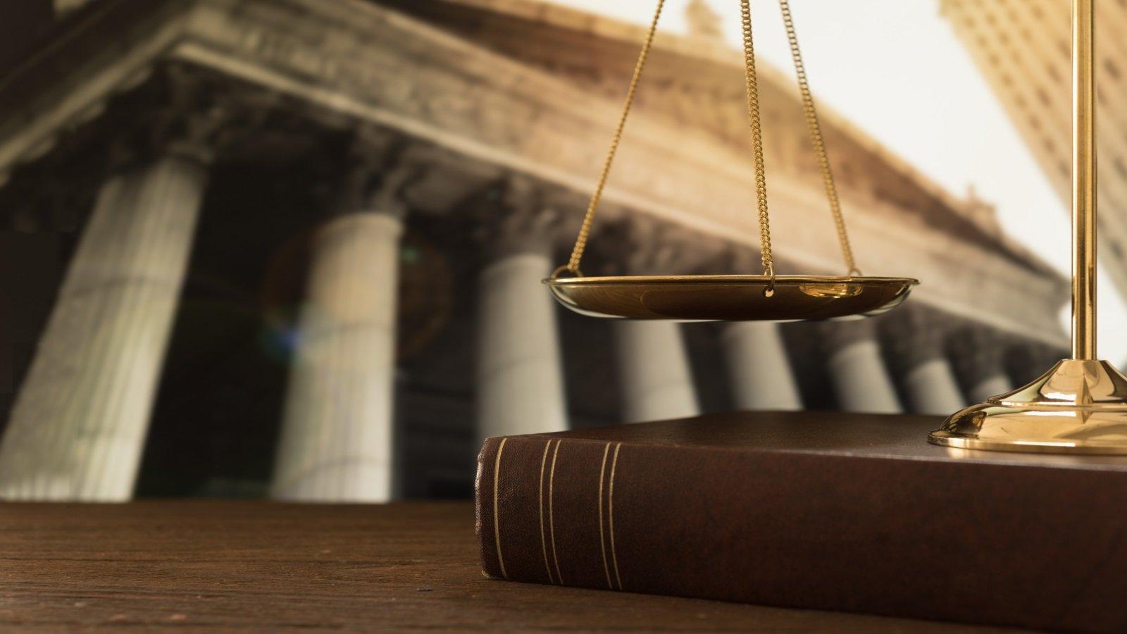 un piatto di una bilancia, un libro e un tribunale