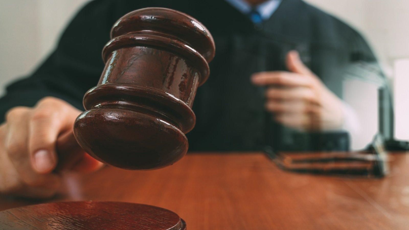 la mano di un giudice con un martello di legno