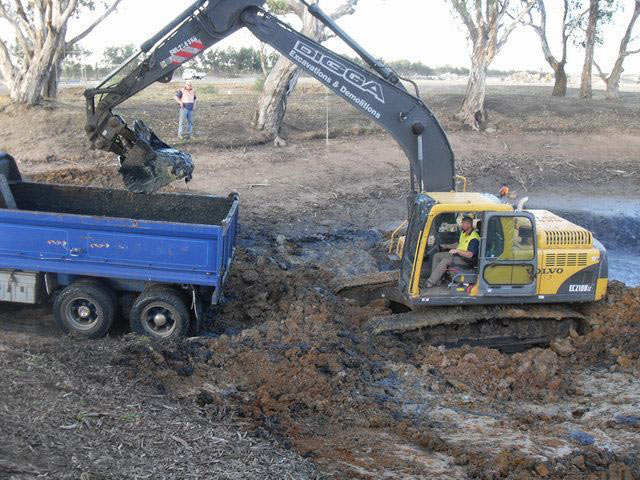 Excavator dumping dirt into truck during an excavation in Geelong