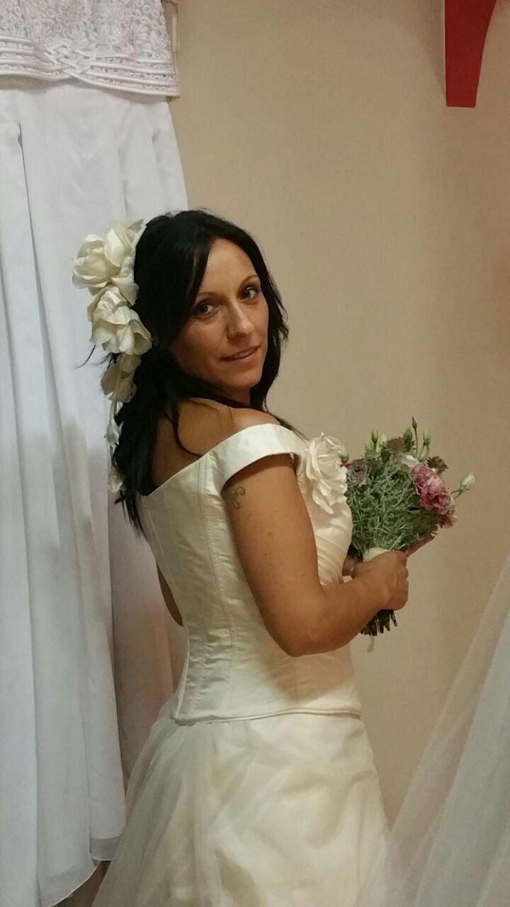 una donna girata di spalle che indossa un abito da sposa  e dietro altri abiti appesi