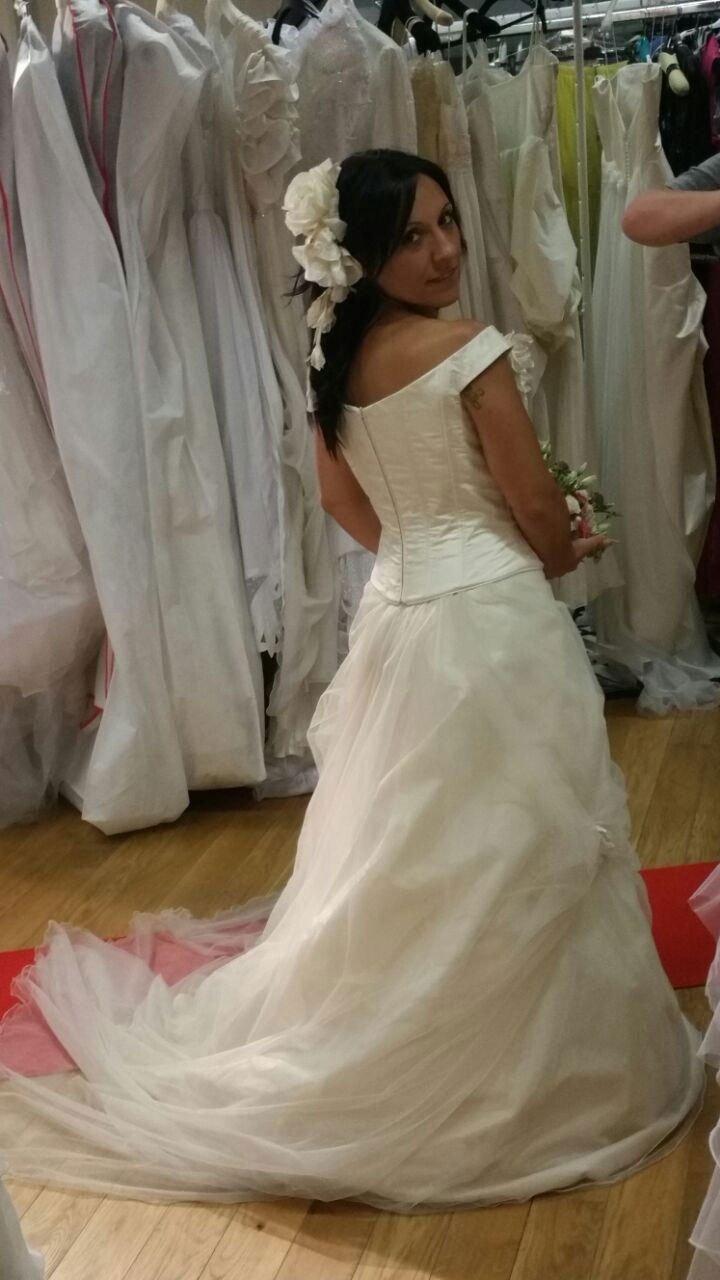 una ragazza in posa con un abito da sposa e dietro diversi abiti appesi