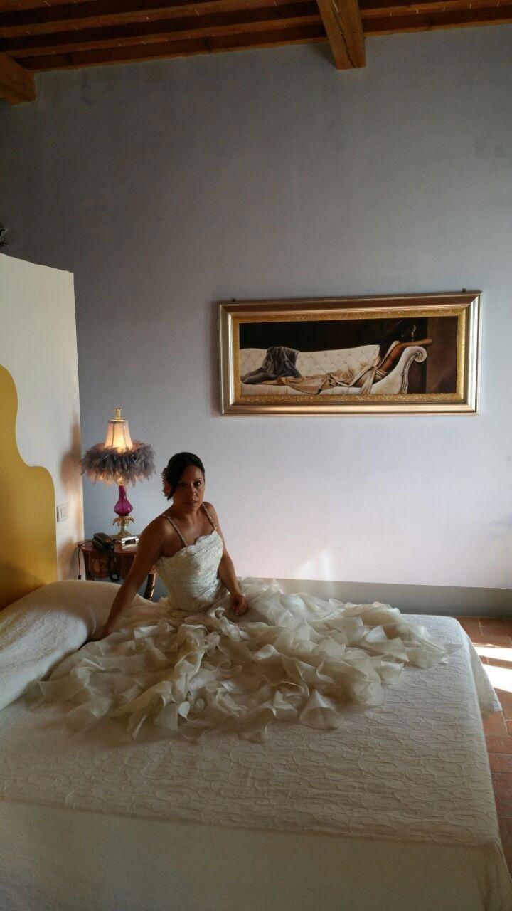 una donna vestita sposa seduta su un letto in una camera con un comodino con sopra una lampada e un quadro sulla parete centrale