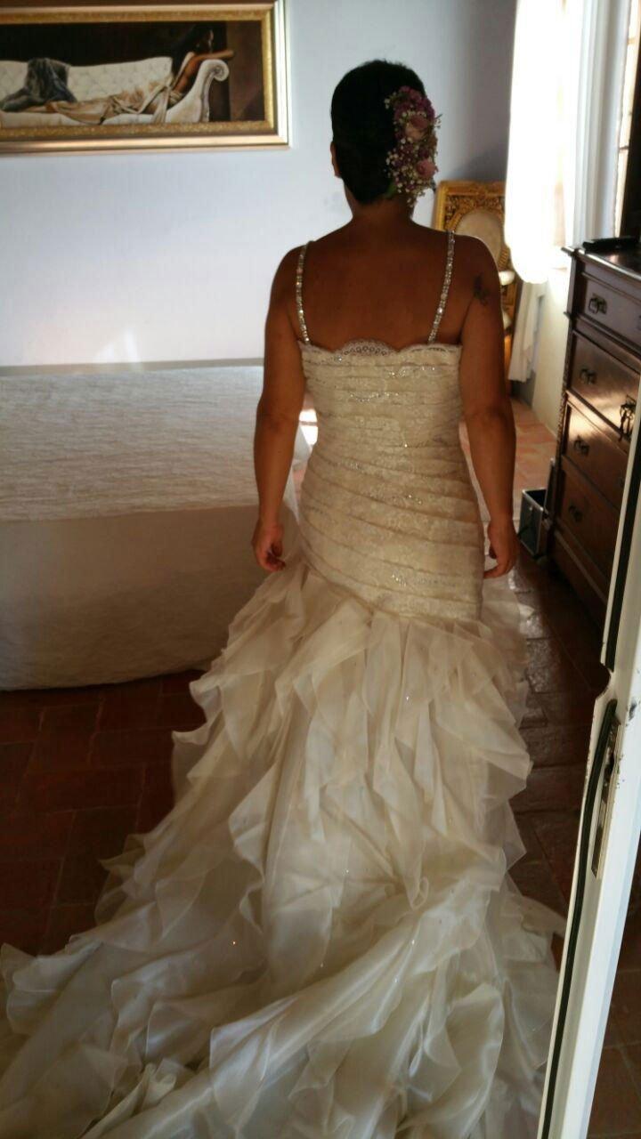 una donna vestita da sposa vista di spalle in una camera con un letto, un comodino con una lampada e un quadro