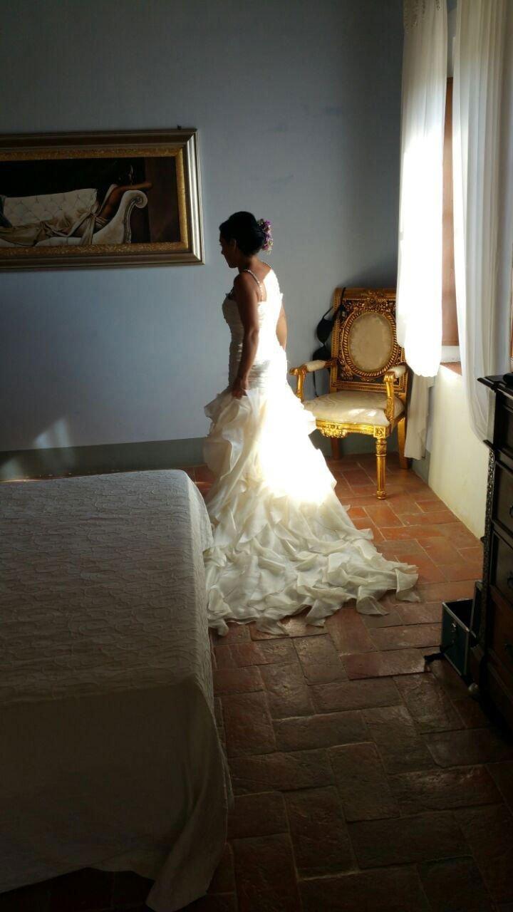 una donna vestita da sposa vista lateralmente in una camera con un letto, un quadro e sulla destra una poltroncina dorata