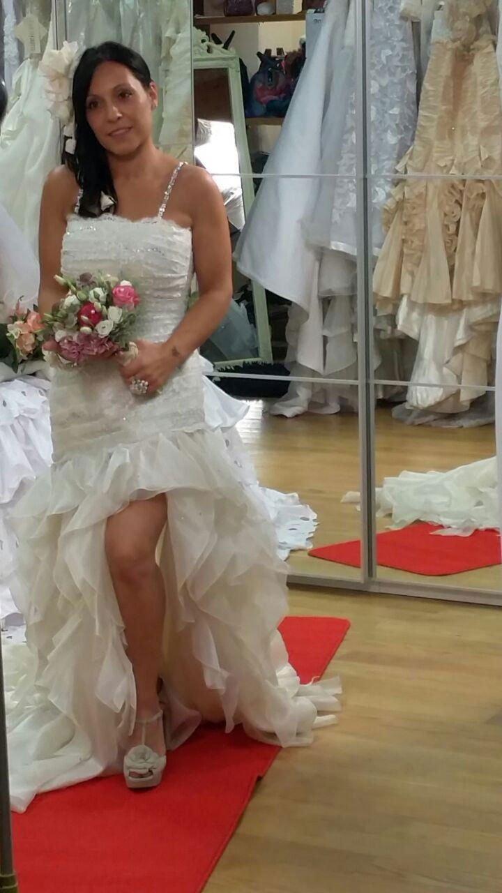 una donna vestita da sposa con in mano un bouquet e dietro uno specchio in cui riflette l'immagine di alcuni vestiti appesi