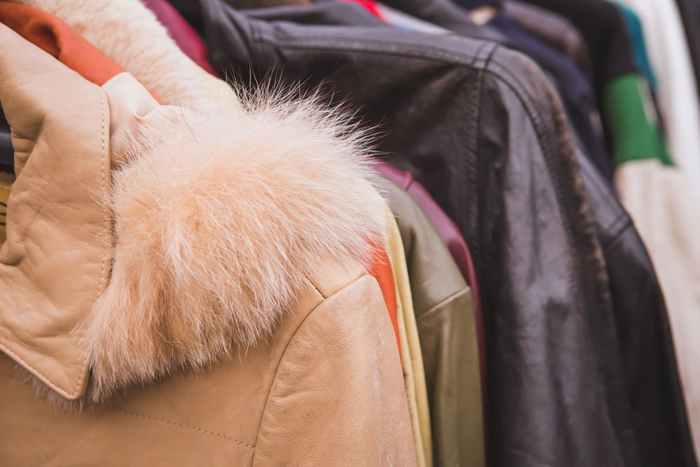 vista del pelo su una giacca beige e dietro altre giacche di diversi tipi