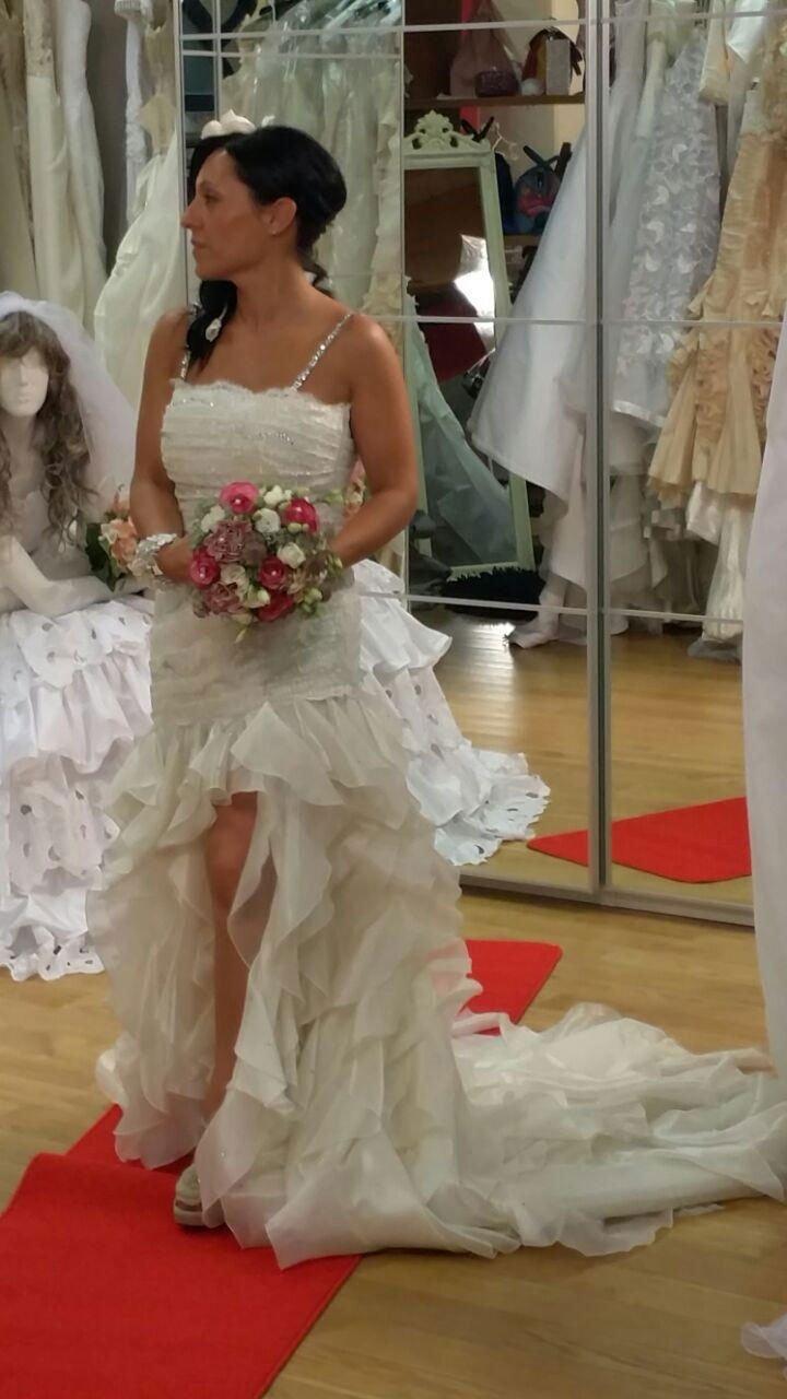 una donna che prova un abito da sposa con in mano un bouquet di fiori