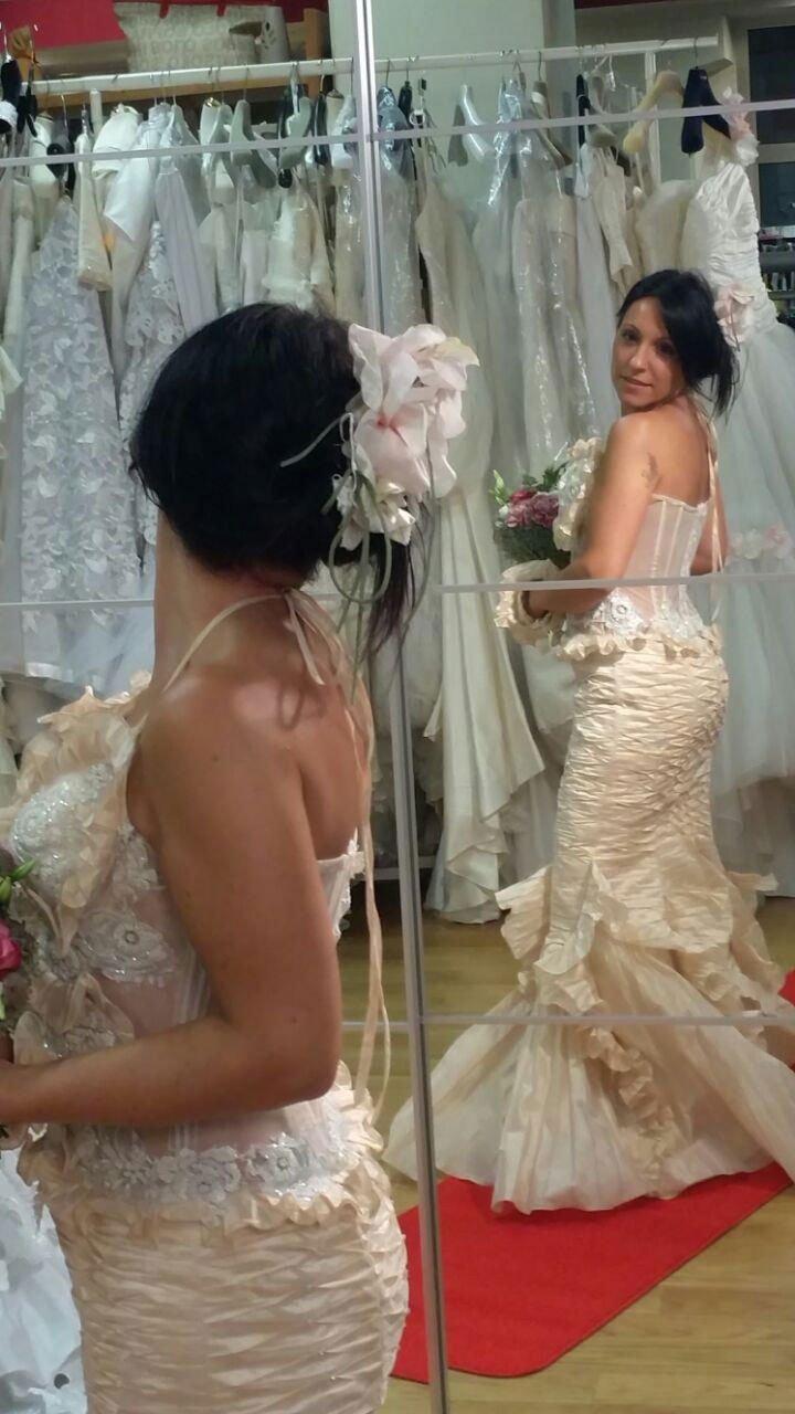 una donna che prova un abito da sposa con in mano un bouquet di fiori di fronte allo specchio