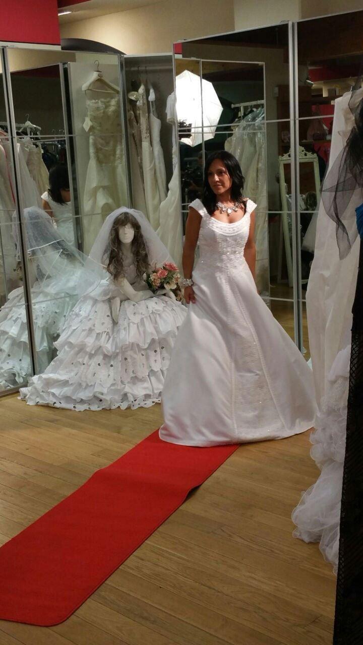 una donna che prova un abito da sposa, dietro un manichinno vestito da sposa e al centro della stanza un tappeto rosso