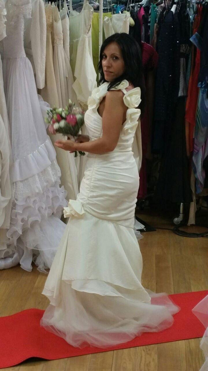 una donna con un abito da sposa, un bouquet di fiori in mano e dietro altri abiti appesi di diversi colori