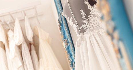 Un manichino con un abito da sposa con il velo lungo di pizzo e dei fiocchi grandi, una parure composta da collana, orecchini e deille scarpe con i tacchi con delle  perline appoggiate sul velo