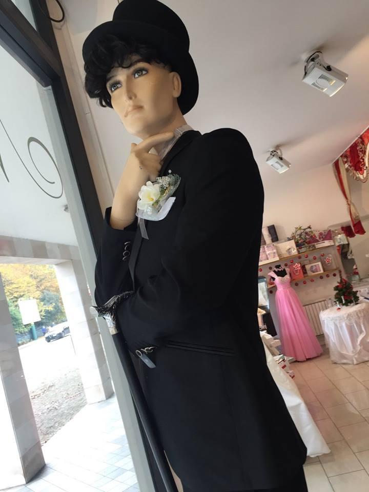 un manichino di un uomo con un cappello, un completo nero con una spilla a  fiori bianchi sulla tasca della giacca e un bastone appoggiato sul braccio