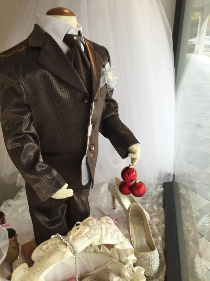 Un manichino con un completo marrone a righe e davanti un paio di scarpe coi tacchi con perline appoggiate su un velo bianco