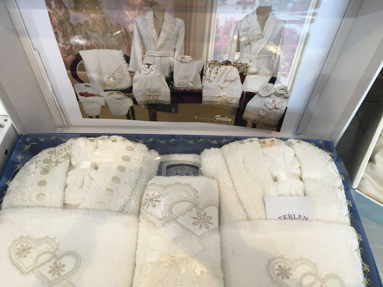 Un set di accappatoi e degli asciugamani da donna e da uomo di color bianco della marca Ferlen