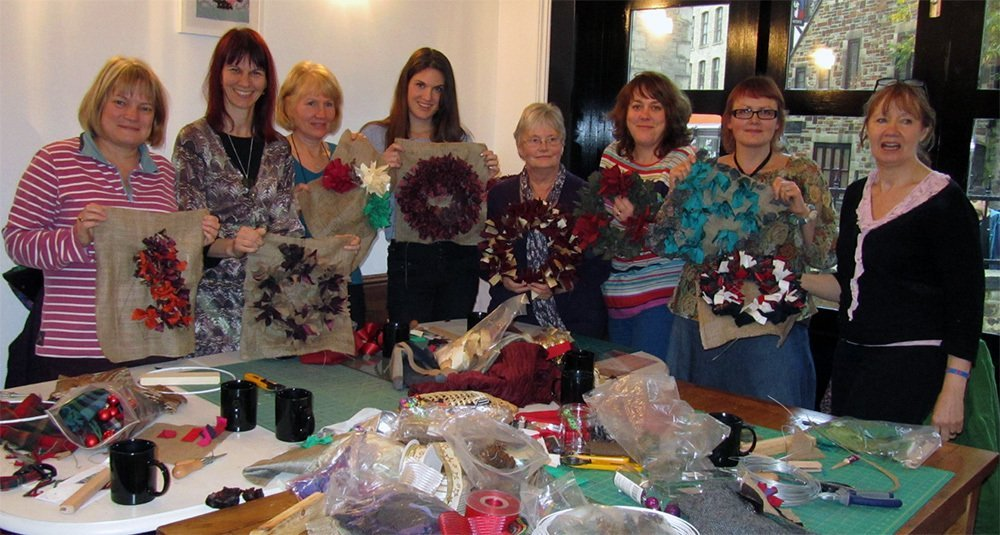 A group showing off craft projects made with quality patchwork materials in Halifax