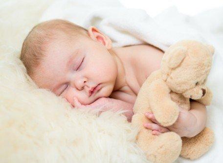 Neonato che dorme abbracciato a un orsetto