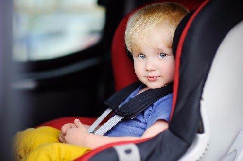 Bambino seduto su un seggiolino in macchina