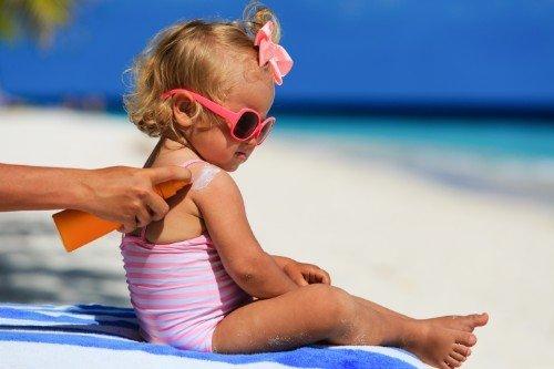 Bambina mentre la mamma gli sta spalmando la crema solare