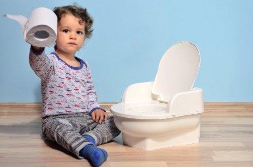 Bambino che tiene in mano un rotolo di carta igienica di fianco a un vasino