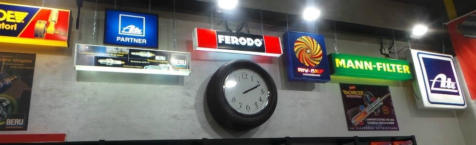 un orologio a muro e delle insegne luminosi di brand importanti di ricambi