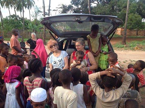 Bambini di fronte a una macchina in un villaggio africano, con volontarie
