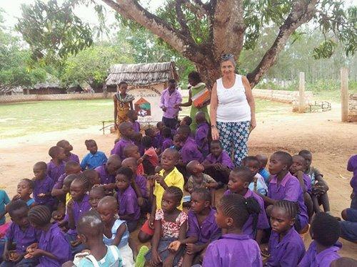 Bambini seduti vicino a un albero con volontaria in piedi