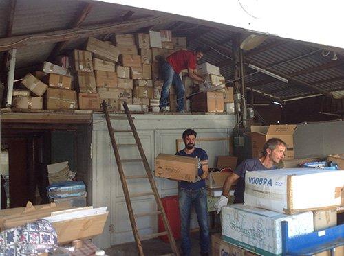 Dei volontari prendono degli scatoloni da un magazzino