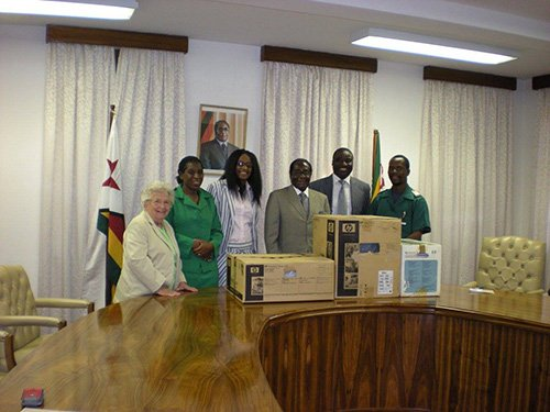 Uomini e donne eleganti in una sala conferenze sorridono di fronte a degli scatoloni
