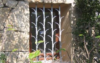 Finestra con ferro protettivo in una costruzione con muro in pietra