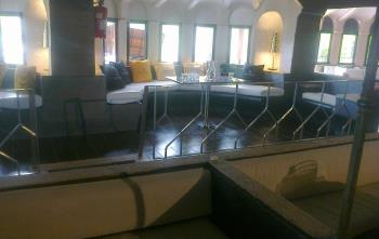 vista interna di una stanza con lungo divano  oltre una ringhiera