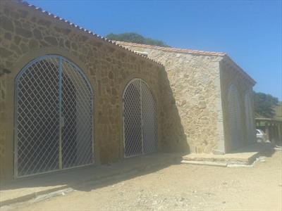 vista laterale di un edifico in pietra  con portoni chiusi da inferriate