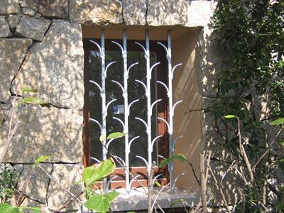 muro di una casa in pietra con inferriate alla finestra
