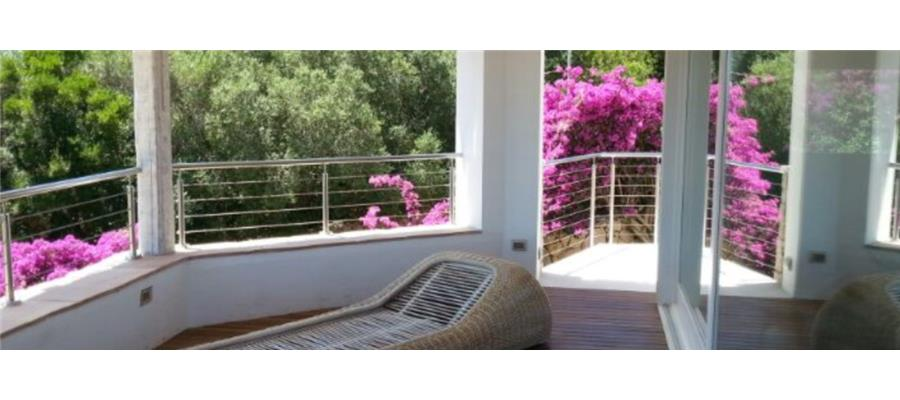 terrazza con sdraio fiori viola e vista su alberi