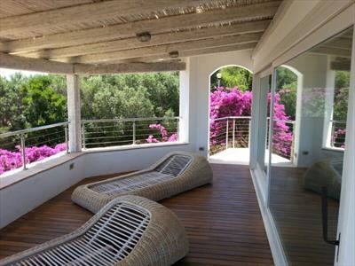 vista di un balcone con ringhiera in vetro e soffitto in legno